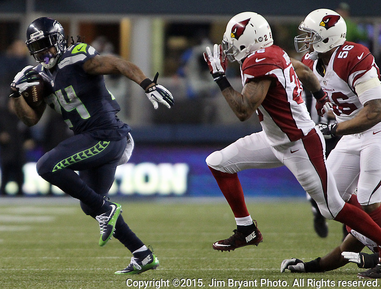 Seattle Seahawks running back Marshawn Lynch rushes past  Arizona Cardinals  Deone Johnson (20) and LaMarr Woodley (56)) at CenturyLink Field in Seattle, Washington on November 15, 2015. The Cardinals beat the Seahawks 39-32.   ©2015. Jim Bryant photo. All Rights Reserved.
