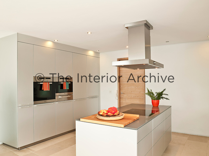 The kitchen is functional with a hob in the central island  and an eye-level oven built into a wall of cupboards