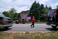 A woman walks by the presidential motorcade press vans, and a car displaying pro-Trump flags , outside  the Trump National Golf Club in Sterling, Virginia, U.S., on Saturday, August 1, 2020. <br /> Credit: Erin Scott / Pool via CNP /MediaPunch