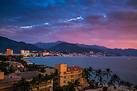 Fine Art Print Photograph of Puerto Vallarta and the beautiful bay of Banderas.<br /> The lighting from the setting sun brought out the details of the buildings and the mirrored reflections from the window glass of the buildings that face the ocean. The background mountains reflect their subtle shades and tonalities. The dramatic skyline lit by the setting sun adds drama to the framing of this photograph.