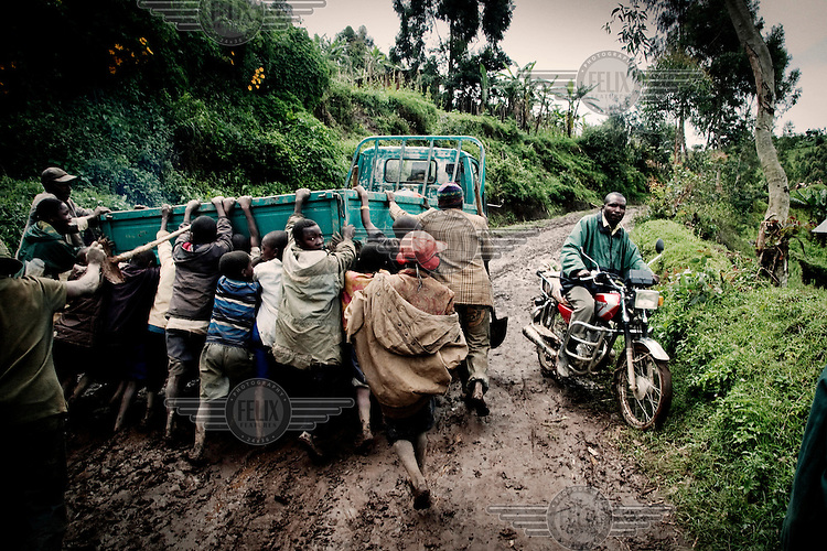 A group of men and boys push a vehicle that has got stuck in a road that has become a quagmire following heavy rain.