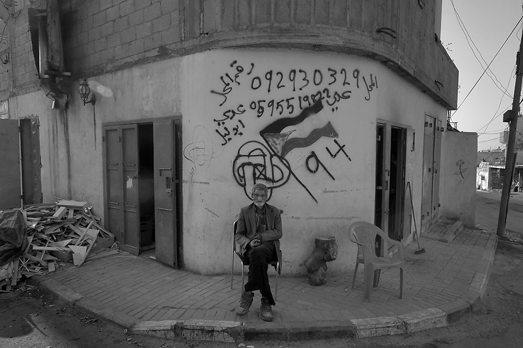 A man at a street corner in Hableh, backdropped by a graffiti referring to the Palestinian bid to the UN to be accepted as the 194 state member.