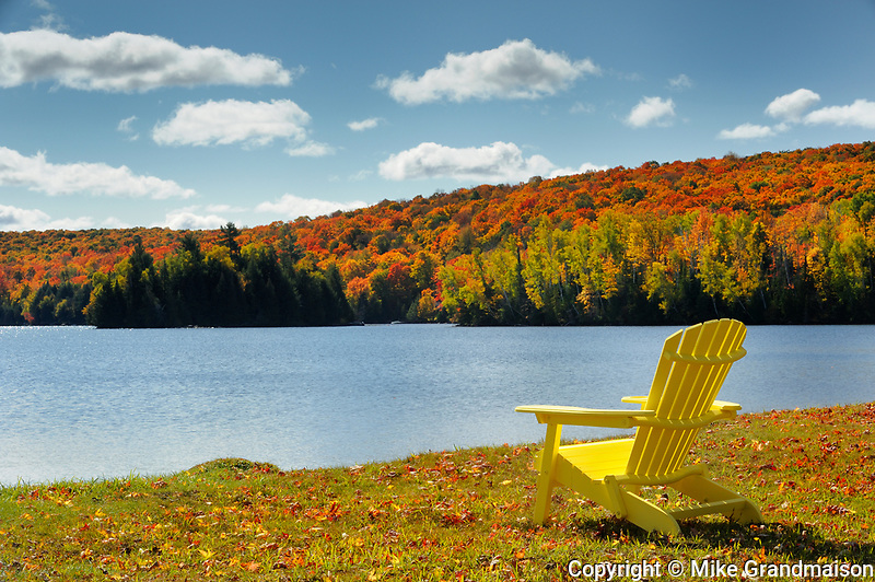 Muskoka chairs on shore of Silent Lake in autumn<br />