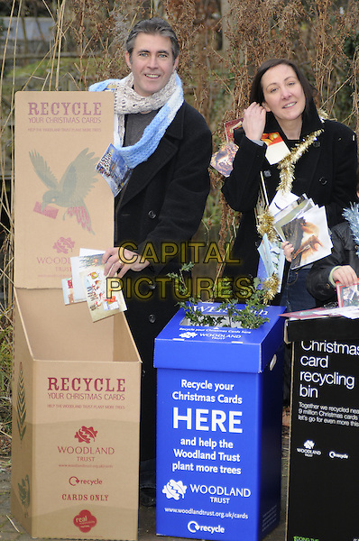 COLIN WELLS & JOANNE MCLEOD  .Launch of the Woodland Trust 2010 Christmas Card Recycling Scheme, The Natural History Museum, London, England..January 5th, 2010.full length recycle cards black coat jacket box blue scarf knitted.CAP/CAN.©Can Nguyen/Capital Pictures.