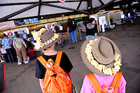 Sisters (11 years old, 8 years old) with Akubra hats and frangipani leis, at Kona International Airport. Big Island, Hawaii