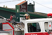 young Joliette, Quebec  firefighter on a fire truck wearing bunker gear at the site of a boutique fire