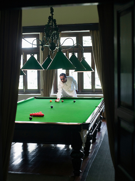 A staff member sets up the billiard table in the Billiard Room, Maharajah's Palace, Ananda in the Himalayas, The Palace Estate, Narendra Nagar, Tehri Garhwal, Uttarakhand, India. The billiard room was restored to its original condition. The billiard table, which was made by C. Lazarus & Co. in Calcutta circa 1820, was once the largest table in area and the first billiard table in the district.