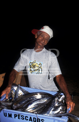 Paraty, Rio de Janeiro, Brazil. Smiling old fisherman wearing a baseball cap woth a crab motif on his t-shirt selling eels.