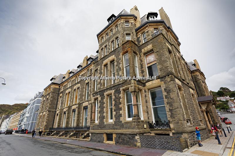 Pictured: Front view of the old Police Station in Aberystwyth, Wales, UK. Wednesday 28 August 2019<br /> Re: Opened 1866, built by the Hafod Hotel Co as the Queens Hotel; architects, Hayward and Davies; builder George Lumley of Aberystwyth. Sold in 1877 and later converted to local government use; remodelled in1950 by G R Bruce, County Architect.<br /> Detached towards N end of the Promenade, with main entrance to side elevation in Albert Place and rear elevation to Queens Road.<br /> Hotel de Ville style. Asymmetrical 3-storey attic and basement snecked rubble 13-bay W (Promenade) elevation; stepped front with mostly vermiculated dressings, stock brick voussoirs, deep entablature and cornice and cill bands; buttresses to ground floor centre. Steep pitch mansard slate roof with truncated chimney stacks. Dormers with steep overhanging roofs and casement windows; paired to left. 3-bays advanced near the right hand end and with additional storey and splayed angles to 2nd floor (with small cast-iron parapets) and 3rd floor; also to top floor) with small cast-iron parapets) and 3rd floor; also to top floor at the corner. Sash windows, some paired; anthemion panelled cast-iron window box holder across central bays.
