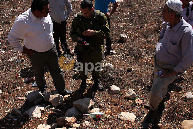 An Israeli soldier talks with Palestinians who attacked by Jewish settlers during pick olives in their agricultural fields in the West Bank village of Hawara, near Nablus. Oct. 10, 2010. Jewish settlers attacked Palestinian farmers during pick olives in their agricultural fields . Photo by Wagdi Eshtayah