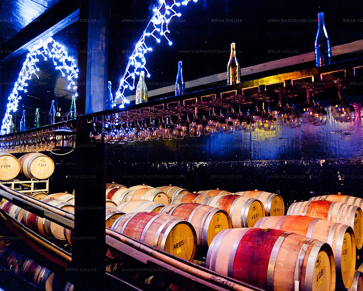 Strings of festive icicle lights cast a glow over the barrels, glasses, and bottles in the barrel room at Ingleside Plantation Winery.