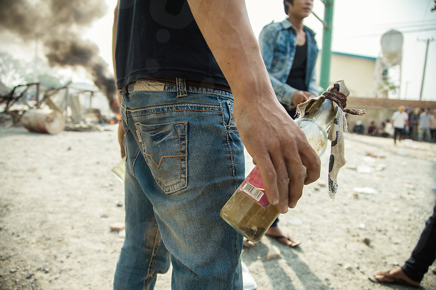 03 January, 2014 - Phnom Penh. A garment factory worker holds a cocktail molotov to throw against the police. © Thomas Cristofoletti / Ruom 2014