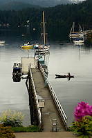 Lone canoe approaches Gallant wharf. Deep Cove, North Vancouver, British Columbia, Canada.