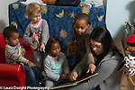 Education Preschool child care 2-3 year olds female teacher reading book to group of boys and girls