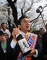 April 7, 2011, Tokyo, Japan - Miki Watanabe, a candidate running for governor of Tokyo, holds a bottle of sake, Japanese rice wine, as he joins revelers in a fest under full-blown cherry blossoms at Tokyo's Ueno Park during his street campaign on Thursday, April 7, 2011. Watanabe, the founder of a chain of casual pubs, is running in the April 10 Tokyo gubernatorial election, attempting to make the big jump from business manager to big-time politician. (Photo by AFLO) [3609] -mis-.