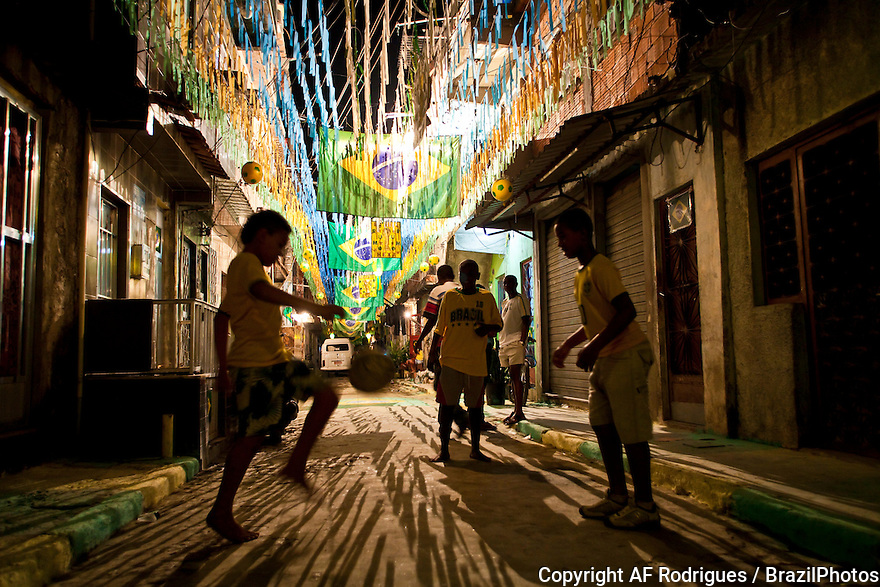 Children play soccer at night in Favela da Mare - street decoration for the World Cup.