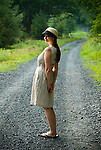 Young woman standing on gravel country road