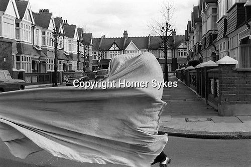 Children playing with bedsheet in the street. Wandsworth SW London UK
