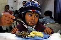 "A girl eats in a soup kitchen named ""Yaveh"" in the shantytown of Villa 31, in Buenos Aires, April 29,2003...In Villa 31 there are about 18 000 poor people, 13 soup kitchens try so serve some food to poor children in the shantytown. After first round elections, Argentineans debate economic plans for the second round between Peronist candidates Kirshner and former President Menem. With an unemployment of 17, 8 % and a poverty rate that has risen to approximately 36 million people, the two candidates will focus there campaign on these issues on next round elections that will be held on May 18. . Photo by Quique Kierszenbaum"