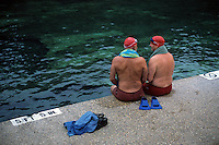 Two red-capped swimmers prepare for a morning dip in Austin's Barton Springs Pool.