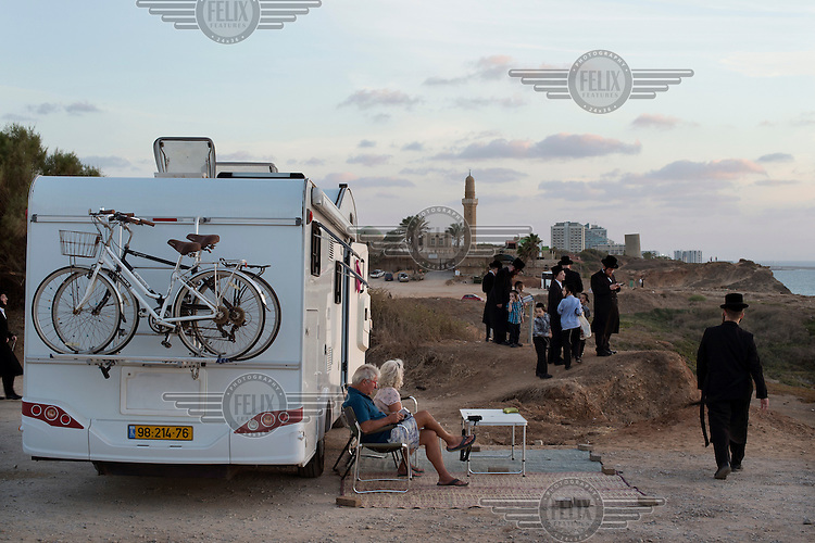 A holidaying couple enjoying the sun outside their caravan as Ultra-Orthodox Jews gather for a 'Tashlich' ritual beside the Mediterranean Sea. 'Tashlich' ('to cast away') is a ritual where believers go to a flowing body of water and symbolically 'throw away' their sins. It takes place before the Day of Atonement ('Yom Kippur'), the holiest day in the Jewish calendar.