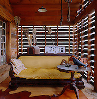 A large wooden sofa upholstered in yellow fabric on the covered porch