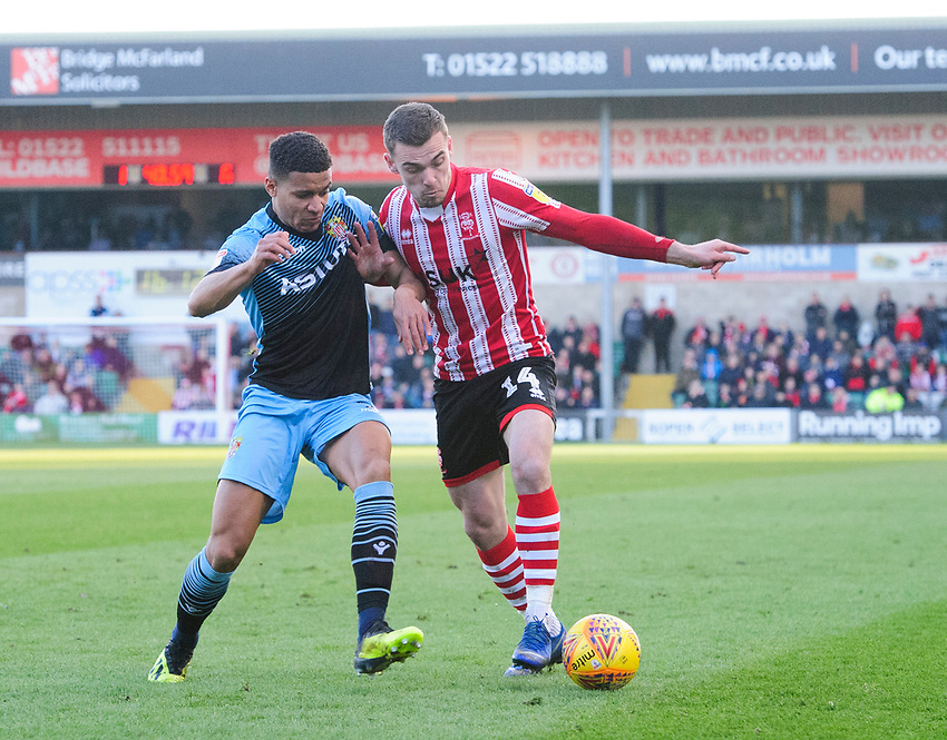 Lincoln City's Harry Toffolo vies for possession with Stevenage's Luther Wildin<br /> <br /> Photographer Chris Vaughan/CameraSport<br /> <br /> The EFL Sky Bet League Two - Lincoln City v Stevenage - Saturday 16th February 2019 - Sincil Bank - Lincoln<br /> <br /> World Copyright © 2019 CameraSport. All rights reserved. 43 Linden Ave. Countesthorpe. Leicester. England. LE8 5PG - Tel: +44 (0) 116 277 4147 - admin@camerasport.com - www.camerasport.com