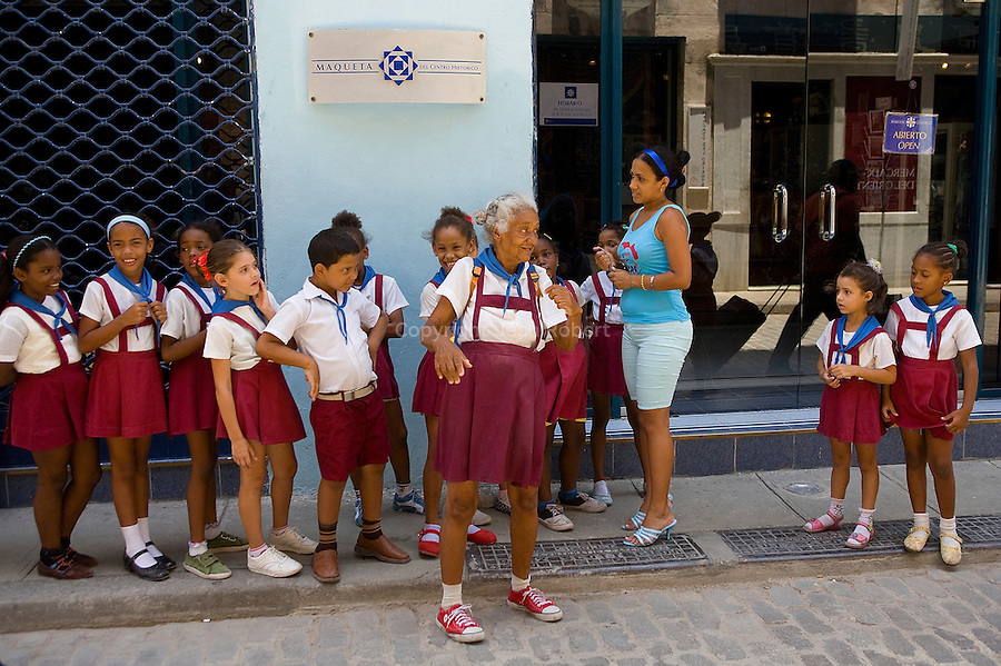 school children of Cuba must wear the same uniform. An excentric old lady is playing with the children in the streets of La Habana