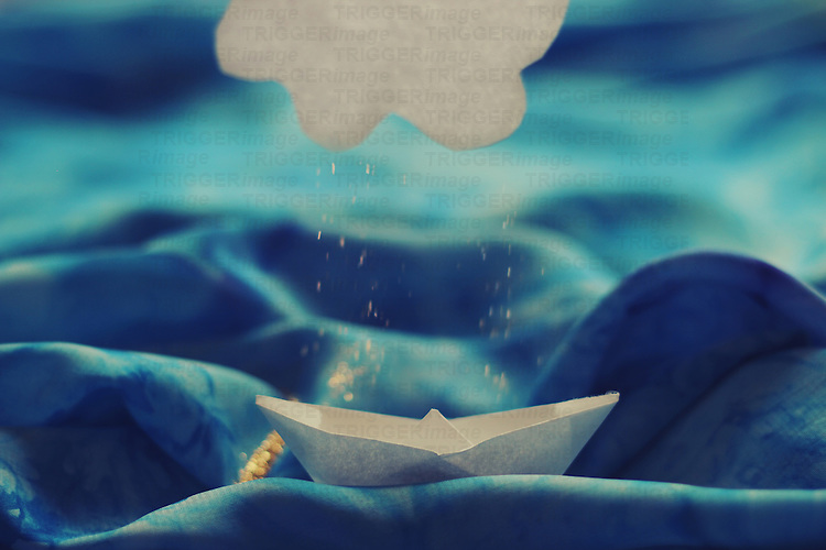 Photograph of a paper boat and cloud over a blue fabric sea with glitter falling over