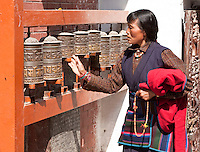 Bodhnath, Nepal.  Buddhist Worshiper Turning Prayer Wheel.