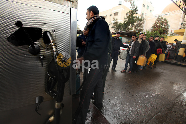 Palestinians fill containers with fuel from a petrol station in the Gaza City on 16 February 2012. Reports state that residents in the Gaza Strip flocked to petrol stations hoping to get a share of the remaining fuel, saying the gas stations in the Gaza Strip are drying up due to the crisis in Egypt and the closing of the fuel lines through the 'smuggling tunnels' between Rafah and the Egyptian side of the border. Photo by Majdi Fathi