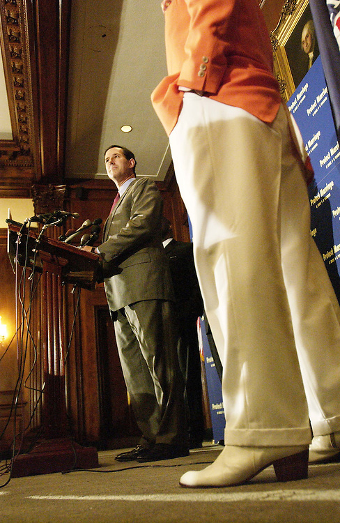 7/13/04.FEDERAL MARRIAGE AMENDMENT--Sen. Rick Santorum, R-Pa., during a news conference on the marriage amendment, which defines marriage as only between one man and one woman, being debated in the Senate. Recording artist Pat Boone's feet are in the foreground..CONGRESSIONAL QUARTERLY PHOTO BY SCOTT J. FERRELL.