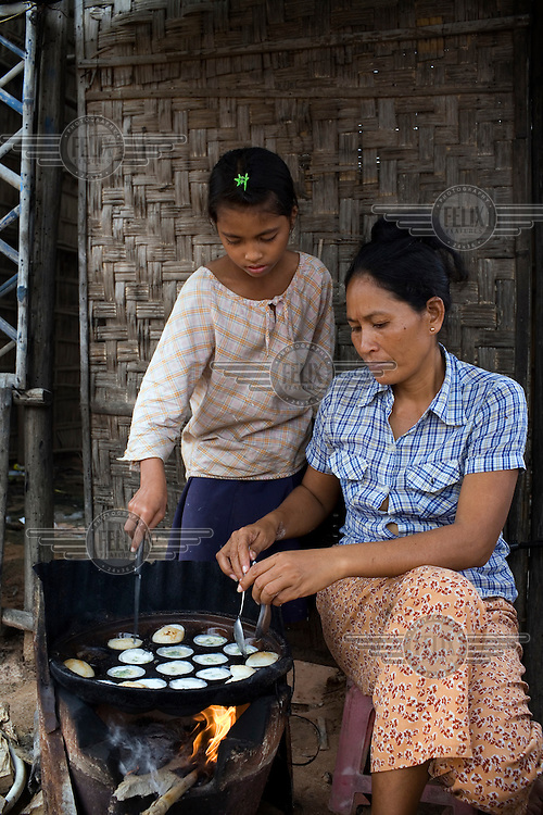 11 year old Chansre Leap has been pulled out of school to help her mother Chenseng Ly make rice cakes at her roadside cafe in An Dong, a suburb of Phnom Penh. The price of the rice flour she uses has doubled in the last year but she is unable to charge her customers any more as she fears they will stop coming.