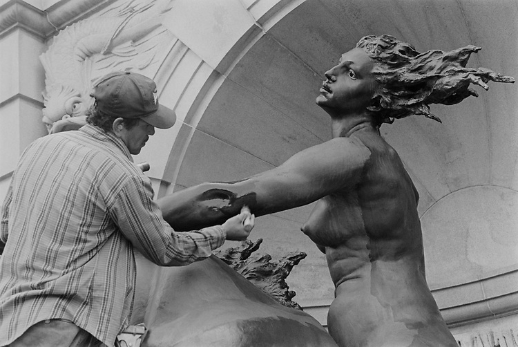 "Michael Lopez, with the office of the Architecture of the Capitol, applying wax to one of the ""Court of Neptune"" statue on July 29, 1993. (Photo by Chris Martin/CQ Roll Call via Getty Images)"