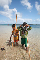 Children playing with starfish in Tonga
