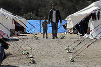 Pictured: A man and his son walk by rows of tents Friday 26 February 2016<br />