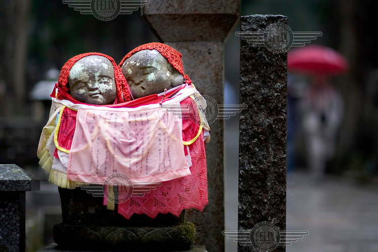 Two Jizo figurines in the Oku-No-in Temple cemetery in Koyasan. These figures are found throughout Japan and are said to protect travellers, children and act as guardians to lost souls. It is common practice to dress them, usually in red, an act that accrues merit in Buddhist cultures. /Felix Features