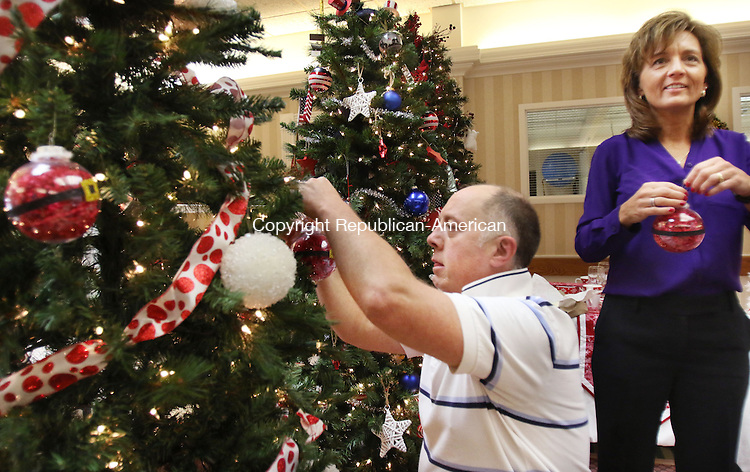 TORRINGTON CT. 23 November 2015-112315SV01-From left, Jonathan Nevin of Torrington and Jennifer Ives-Groebl of Torrington decorate the Litchfield Bancorp tree at Valerie Manor in Torrington Monday. The annual Festival of Trees kicks off Tuesday with a preview party. The event raises money for LARC. <br /> Steven Valenti Republican-American