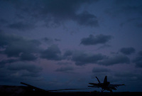 An F/A-18 recovers aboard USS Carl Vinson as night falls in the Indian Ocean.