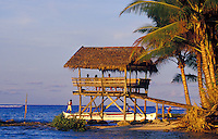 People in thatched hut on the ocean with outrigger canoe unloading surfers, Siargao Island, Philippines