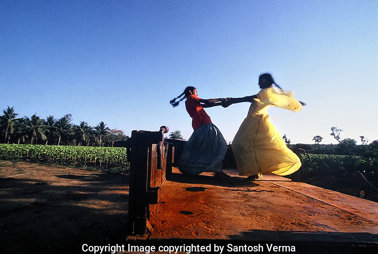Two young girls, play 'FUGDI' the local, indian version of merry-go-round' on the back of an empty tractor trailer near a tobacco farm in South India. Photograph © Santosh Verma