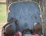 Students at a chalkboard leaning against a tree in an outdoor class in the Loreto Primary School in Rumbek, South Sudan. While focused on educating girls from throughout the war-torn country, the school, run by the Institute for the Blessed Virgin Mary--the Loreto Sisters--of Ireland, also educates children from nearby communities.