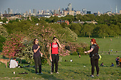 Covid-19 pandemic.  A  police officer orders sunbathers to take exercise or leave the park.  Primrose Hill, London, where lockdown rules regarding social distancing, sun-bathing and picnicing are not consistently observed.