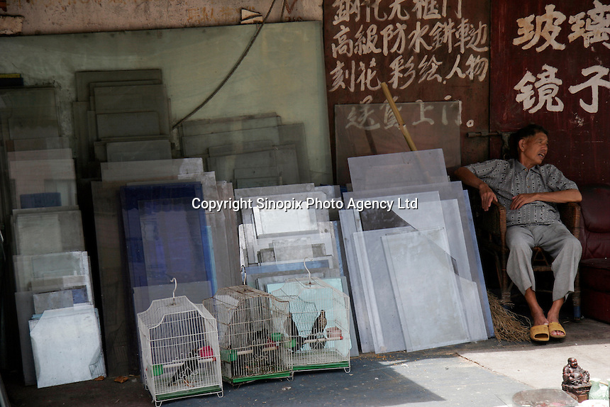 An elderly man sleeps near a glass workshop in Shanghai, China..16 Jun 2005