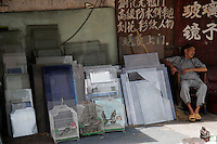 An elderly man sleeps near a glass workshop in Shanghai, China..16 Jun 2005