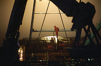 "Standing on top of a stack of crab pots, framed by the crane, crewman Troy Painter of the fishing vessel ""Kiska Sea"" looks over the bow searching for buoys while opilio crab fishing in the Bering Sea.  The Bering Sea is known for having the worst storms in the world.  Nights are long and cold in the arctic in the winter.  Crab fishing in the Bering Sea is considered to be one of the most dangerous jobs in the world.  This fishery is managed by the Alaska Department of Fish and Game and is a sustainable fishery.  The Discovery Channel produced a TV series called ""The Deadliest Catch"" which popularized this fishery."