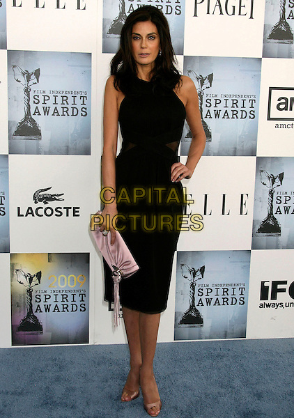 TERI HATCHER.2009 Film Independent Spirit Awards held at the Santa Monica Pier, Santa Monica, California, USA..February 21st, 2009.full length black dress hand on hip pale pink clutch bag bronze open toe shoes mesh sides jewelled gold beige .CAP/ADM/MJ.©Michael Jade/AdMedia/Capital Pictures.