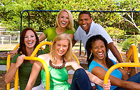 Great group of mixed ethnic friends having fun andf laughing at playground on ride outdoors in sunshine