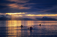 Sea kayakers paddle into the sunset in Prince William Sound, Alaska.