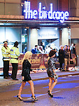 © Joel Goodman - 07973 332324 . No syndication permitted . 01/01/2014 . Manchester , UK . Two women cross the road outside the Birdcage nightclub as police look on . Revellers see in the New Year in Manchester today (January 1st 2014) as police report that officers are at full stretch responding to calls . Photo credit : Joel Goodman